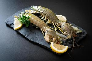 frische Fangschreckenkrebse mit Zitrone auf einem Brett foto