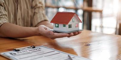 immobilienmakler mit hausmodell auf hans angebotshaus. Sachversicherung und Sicherheitskonzept foto