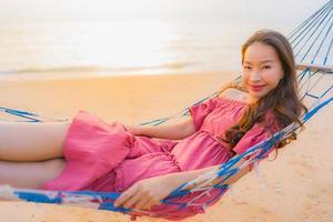 Porträt schöne junge asiatische Frau sitzt auf der Hängematte mit einem Lächeln glücklich in der Nähe von Strand Meer und Ozean foto