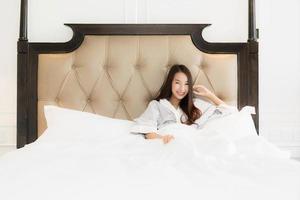 Porträt schöne junge asiatische Frau wacht glücklich auf und lächelt auf dem Bett im Schlafzimmerinnenraum foto