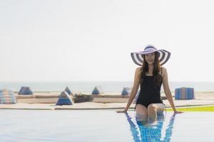 schöne junge asiatische frau glückliches lächeln und entspannen im pool foto