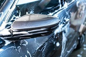 Nahaufnahme Autoseitenspiegel mit Autowaschschaum foto
