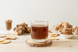 heißes und süßes Ingwersaftglas mit Ingwerwurzeln - gesunde Getränkeart foto