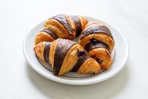 frisches Croissant mit Schokolade auf Teller foto