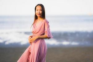 Porträt junge schöne asiatische Frau Spaziergang Lächeln und glücklich am Strand Meer und Ozean foto