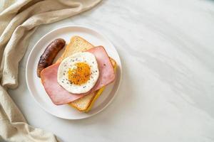 hausgemachtes Brot, gerösteter Käse, belegter Schinken und Spiegelei mit Schweinswurst zum Frühstück foto