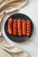 frittierter Wurstspieß auf schwarzem Teller foto