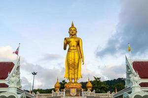 eine goldene buddha-statue mit dem himmel auf dem berggipfel im öffentlichen park der gemeinde hat yai, provinz songkhla, thailand foto