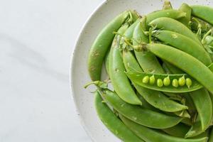 frische süße grüne Erbsen auf weißem Teller foto