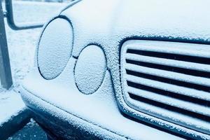 blauer Frost und Eis auf Autoscheinwerfern - frostiger Wintermorgen - Kaltstart foto