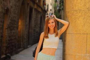 junge lächelnde frau, die auf den straßen von barcelona spaziert, steinhintergrund, lauter schuss, sonnenuntergangszeit foto