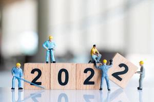 Miniatur-Leute-Arbeiter-Team erstellen Holzblock Nummer 2022 foto
