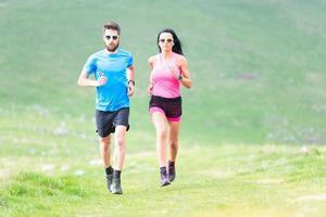 Aktion von Läufern auf hügeligen Wiesen im Sommer. Mann und Frau foto