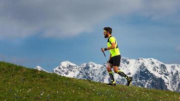 Nordic Walking und Trailrunning ein Mann mit Stöcken auf Frühlingsbrasse mit schneebedecktem Hintergrund foto