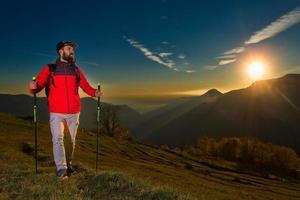 junger Mann mit Bart, der das Panorama beobachtet, ruht sich während einer Nordic Walking-Wanderung aus foto