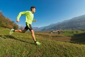 Sportler läuft bergab auf der Wiese in einem Tal der italienischen Alpen. foto