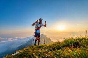 Mann mit Stangen in den Bergen mit Sonnenuntergang dahinter foto