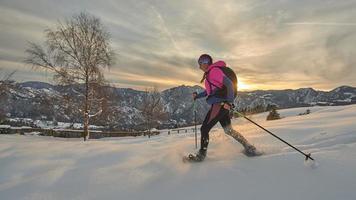 ein Schneeschuhmädchen in einem wunderschönen Wintersonnenuntergang foto