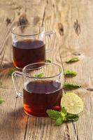 Tasse Tee mit Ingwer, Zitrone und Minze auf Holztisch foto