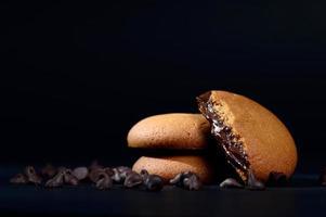 Kekse gefüllt mit Schokoladencreme. Schokoladencreme-Kekse. braune Schokoladenkekse mit Sahnefüllung auf schwarzem Hintergrund. foto