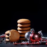 Kekse - Stapel köstlicher Sahnekekse gefüllt mit Schokoladencreme, verziert mit Weihnachtsschmuck auf schwarzem Hintergrund foto