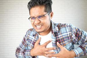junger Mann, der Schmerzen im Herzen leidet und Brust mit Hand hält foto