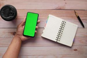 Draufsicht der Mannhand unter Verwendung des Smartphones am Schreibtisch foto