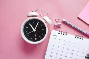 Terminkonzept mit Kalender und Wecker auf Rosa foto