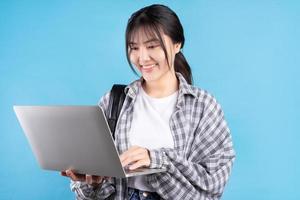 asiatische Studentin mit verspieltem Ausdruck auf blauem Hintergrund foto