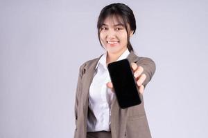 junge asiatische Geschäftsfrau mit Telefon auf weißem Hintergrund foto