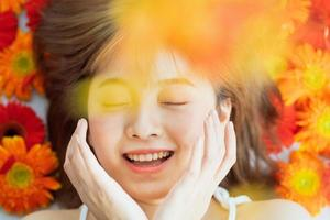 junges Mädchen, das auf einer Blume mit einem glücklichen Ausdruck liegt foto