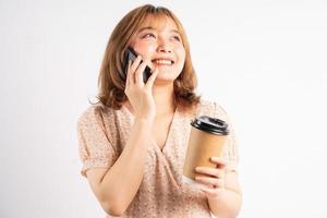 junges Mädchen, das Kaffeetasse hält und im Hintergrund Telefon hört foto