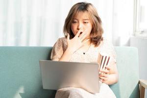 junges asiatisches Mädchen, das auf dem Sofa sitzt und Filme auf dem Laptop isst und schaut foto
