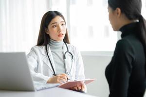 asiatische Ärztin untersucht Patienten in der Klinik foto
