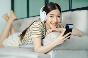 schöne asiatische frau, die auf dem sofa liegt und musik hört, während sie telefon benutzt foto