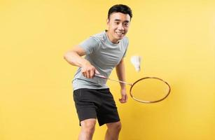 asiatischer Mann, der Badminton auf gelbem Hintergrund spielt foto