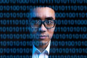Porträt des asiatischen Geschäftsmannes mit Codezeilen auf seinem Gesicht. Menschenbild der Zukunft digitalisiert foto