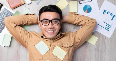 asiatischer Mann fühlt sich glücklich, wenn er die Arbeit pünktlich fertigstellt foto