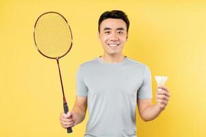 Porträt eines asiatischen Mannes, der einen Badmintonschläger auf gelbem Hintergrund hält foto