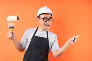 asiatischer Maler mit Pinsel posiert auf orangem Hintergrund foto