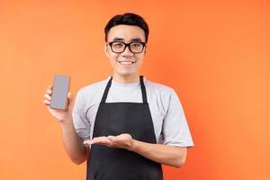 Porträt des asiatischen männlichen Kellners, der auf orangem Hintergrund posiert foto
