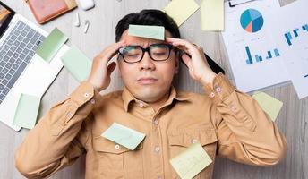 asiatischer Mann liegt auf einem Stapel Papiere und fühlt sich müde von der Arbeit foto