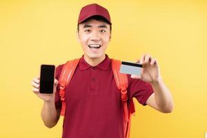 asiatischer Lieferbote, der eine rote Uniform trägt, die auf gelbem Hintergrund posiert foto