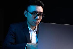 Porträt eines asiatischen männlichen Programmierers, der nachts arbeitet foto