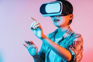 Junge Asiatin trägt eine VR-Brille, um Augmented-Reality-Technologie zu erleben foto