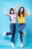 Ganzkörperporträt von zwei schönen jungen asiatischen Mädchen auf blauem Hintergrund foto