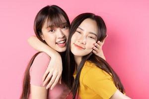 Porträt von zwei schönen jungen asiatischen Mädchen, die auf rosa Hintergrund posieren foto