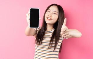 junge asiatische Frau mit Smartphone auf rosa Hintergrund foto