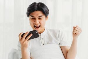 asiatischer Mann, der im Bett sitzt und Spiel spielt. Der asiatische Mann freut sich über den Sieg beim Spielen des Handyspiels playing foto