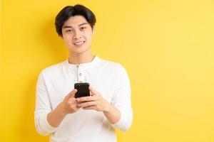 asiatischer Mann, der sein Telefon benutzt, um auf gelbem Hintergrund zu schreiben foto